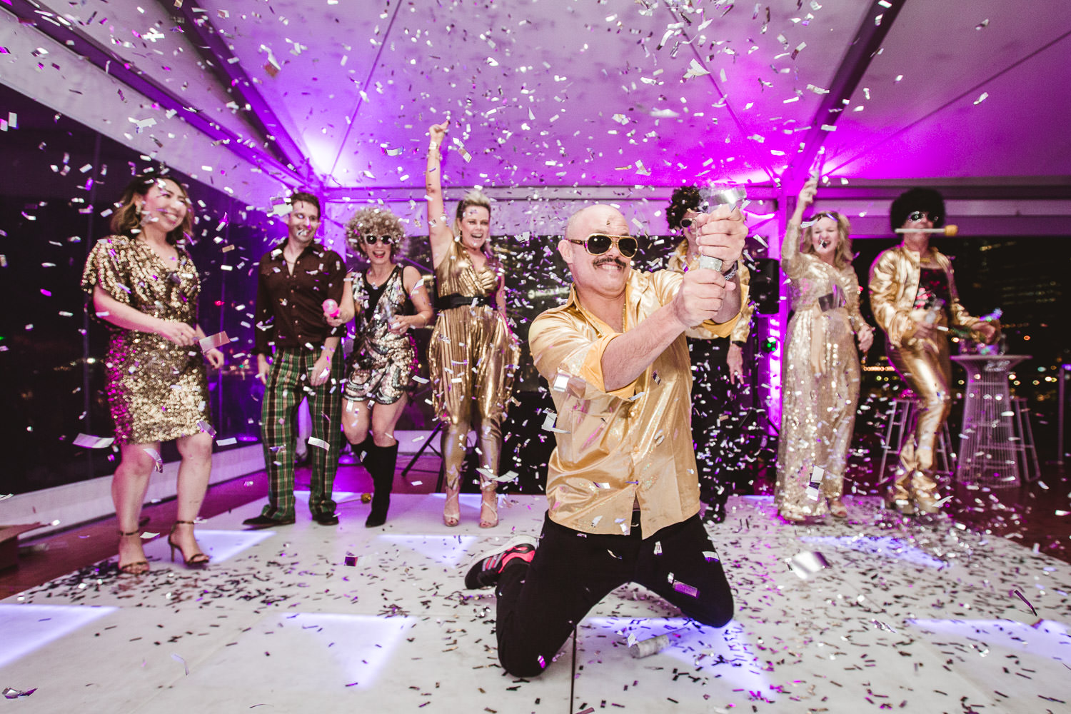 Commercial - Events - A bald man dressed in a gold shirt kneels at the front of a dancefloor, while surrounded by silver confetti and seven other people dressed in gold